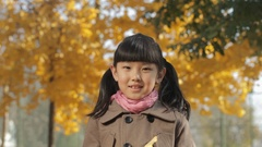 CU Portrait of girl throwing dry leaves above her head in park / China Stock Footage