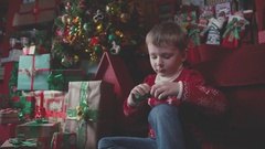Portrait of a young boy near the Christmas tree with a gift Stock Footage