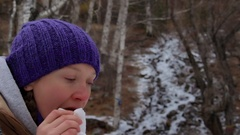 Girl eating cake and drinks tea at a stream in the winter woods Stock Footage