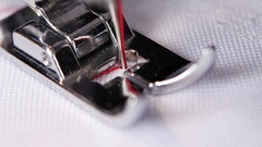 Sewing machine makes a red thread stitch in slow motion Stock Footage