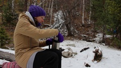 Young woman pours tea from a thermos near a stream in the winter forest Stock Footage