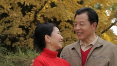 CU Elderly couple laughing, standing in park / China Stock Footage