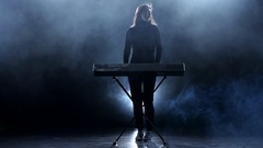 Musician woman playing the piano. Studio. Smoke Stock Footage
