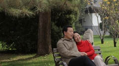 MS Elderly couple talking, sitting and embracing on park bench / China Stock Footage