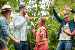 Happy friends dancing at summer party in garden Stock Photos