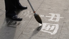 CU Man writing Chinese calligraphy on pavement with water / Beijing, China Stock Footage