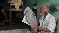 MS TU Man sitting in front of barber shop / Varanasi, India Stock Footage