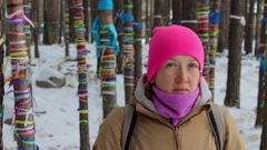Portrait of a girl in the winter forest among the trees with colored ribbons Stock Footage