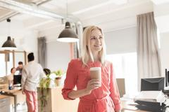 Happy creative female office worker with coffe cup Stock Photos