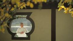 MS SELECTIVE FOCUS View through gazebo's window of mature man doing Tai Chi / Stock Footage