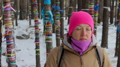Girl meditates in the winter forest among the trees with colored ribbons Stock Footage