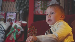 The boy with chubby cheeks eating colorful round Christmas candy Stock Footage