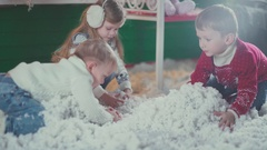 Three child play with feathers or cotton simulating snow Stock Footage