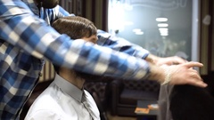Long hair barber is doing a haircut to young bearded man in barbershop. 4K Stock Footage