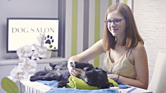 Woman caressing cute dog lying at dog salon and smiling in camera 4K Stock Footage