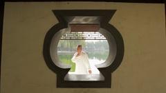 MS ZI View through gazebo's window of mature man doing Tai Chi / Beijing, China Stock Footage