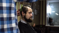 Long hair Barber cuts the hair of the client with scissors and comb in his Stock Footage
