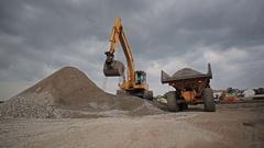Backhoe loader loading sand on a tipper truck Stock Footage