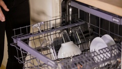 Pulling out a top shelf in the dishwasher and placing on it a few items  Stock Footage