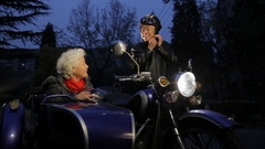 WS Elderly couple getting ready to ride a motorcycle with sidecar at night / Stock Footage