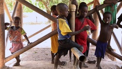 Kids hanging in the pipes of water deposit - native village Guinea Africa Stock Footage