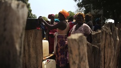 Women in a foutain filling buckets of water- village Guinea Africa Stock Footage