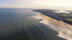 Aerial fast forward shot of beautiful British town surrounded by sea, UK Stock Footage