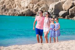 Happy beautiful family with kids walking together on tropical beach during Stock Photos