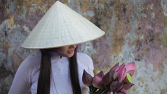 MH LD Young Woman Wearing Ao Dai and Straw Hat Holding Flowers / Hoi An, Vietnam Stock Footage