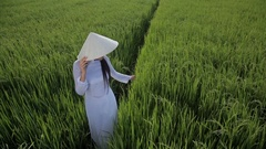 WS HA LD Young Woman Wearing Ao Dai Standing in Rice Paddy / Vietnam Stock Footage