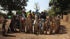 Women filling buckets of water in foutain - village Guinea Africa Stock Footage
