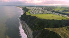 Aerial view of coastline cliffs revealing holiday homes caravan park on top, UK Stock Footage