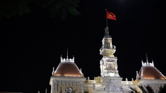 MH LA LD Vietnamese Flag Waving from Top of Ho Chi Minh City Hall at Night / Ho Stock Footage