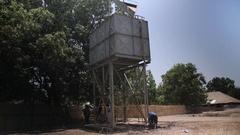 Men drinking from bad water deposit in village - Guinea Africa Stock Footage