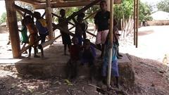 Kids in water deposit structure - native village  Guinea Stock Footage