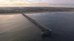 Aerial view of bridge in the sea, flying towards coast, UK Stock Footage