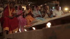 WS LA Woman wearing saris and clapping, candles in foreground / Varanasi, India Stock Footage