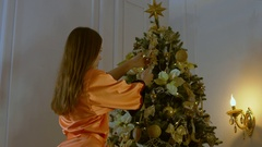 4K CINEMAGRAPH - seamless loop. Young Caucasian girl decorating a Christmas tree Stock Footage