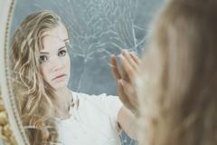Woman reflection in broken mirror Stock Photos