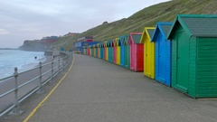 Row of colorful beach huts with people walking in distance, Whitby, UK Stock Footage