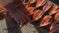 CU LD Woman Laying Fish out on Beach to Dry / Vietnam Stock Footage
