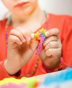 Girl weaves jewelry bracelet gum, weaving Stock Photos