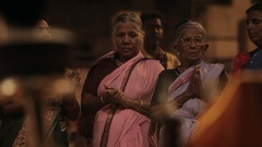 MS Women wearing saris and clapping, incense burning in foreground / Varanasi, Stock Footage