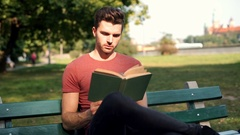 Man answers cellphone while reading book in the park Stock Footage