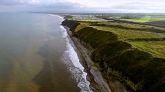 Aerial view of coastline with high cliffs, flying forward revealing caravan site Stock Footage