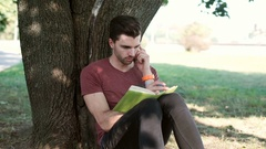 Man talking on cellphone while leaning on a tree and writing something down Stock Footage