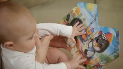 Mother 40 years old reading a book a small child sitting on the couch Stock Footage