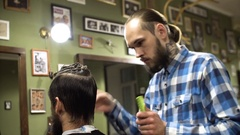 Attractive young barber is cutting human hair with the scissors. He is looking Stock Footage