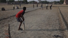 WS Young Boys Playing Cricket in Dirt Field / India Stock Footage