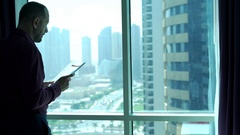 Young businessman reading, analyzing documents standing by window at home Stock Footage